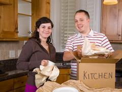Couple moving house in kitchen packing boxes