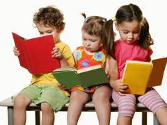 Three preschool aged girls reading books while sitting on a chair