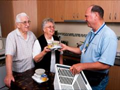 Male Staff delivering Food parcel to older couple
