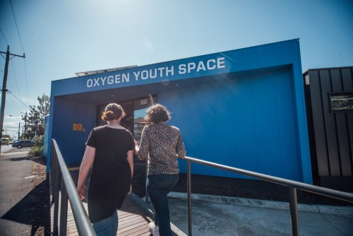 Two young people walking into Oxygen Youth Space